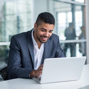 good web hosting company photo of a man smiling using his laptop